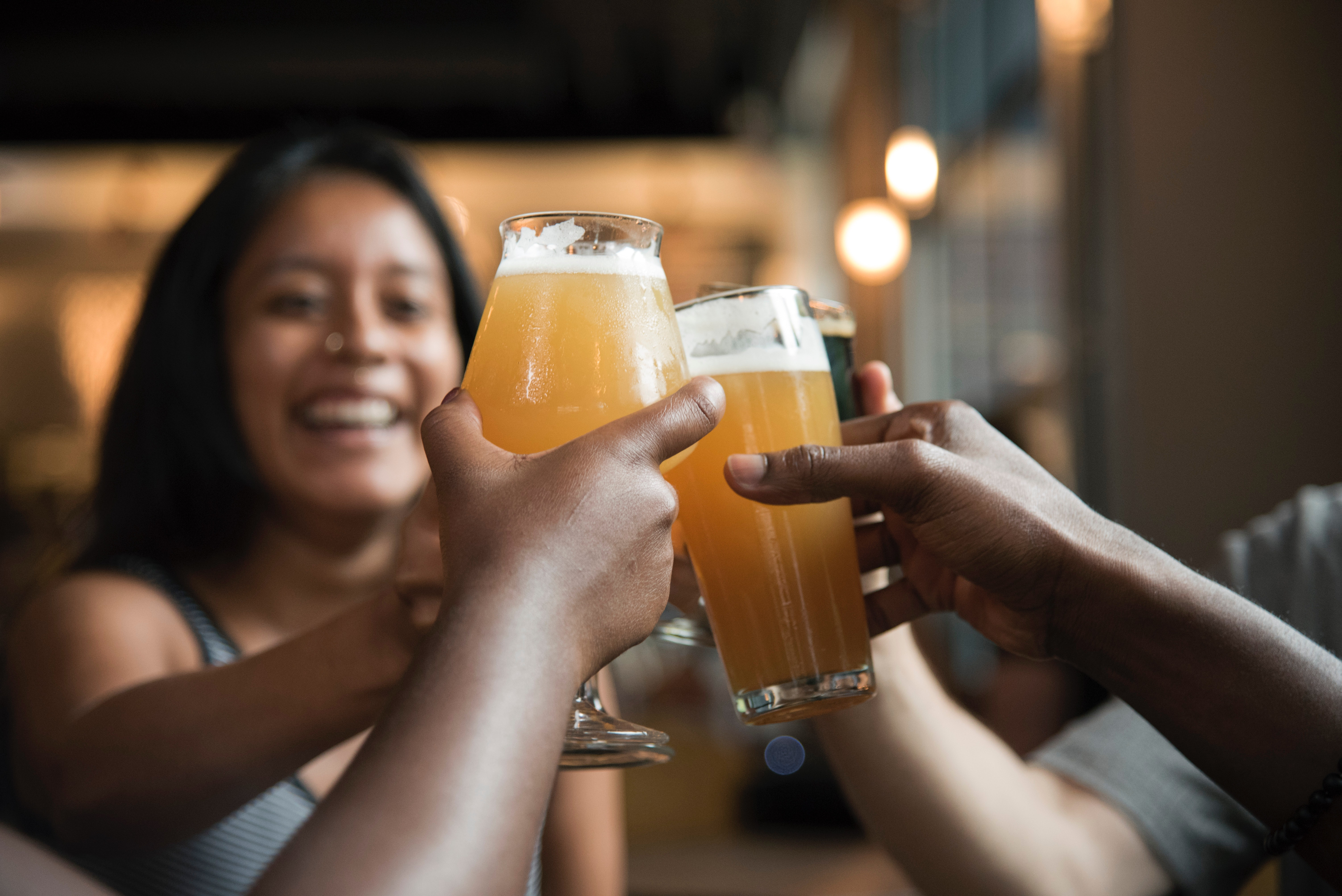 Close up photo of hands toasting beer glasses with smiling woman's face in background