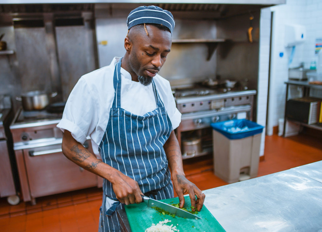 photo of a black man with tattoos on his arms wearing a matching blue-striped apron and chef hat cutting onions in an industrial kitchen setting