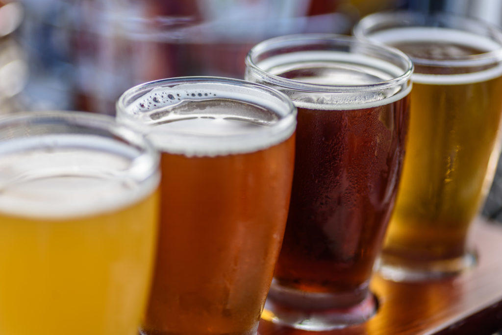 close up photo of 4 small beer glasses filled with beers of varying shades from light yellow to dark brown